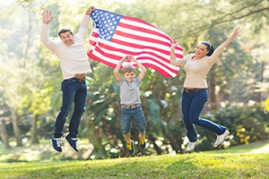 family jumping with USA flag