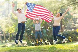 Family waving and American flag after the received their Green Cards