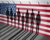 immigrant shadows against an American flag wall topped with barbed-wire