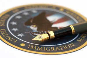 pen over immigration services seal